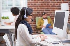 Starke zufällige junge Frau, die Computer verwendet Stockfoto