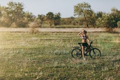 Starken Blondine in einer bunten Klage sitzen auf einem Fahrrad in einem Wüstengebiet mit Bäumen und grünem Gras und betrachten d Stockfotografie