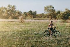 Starken Blondine in einer bunten Klage sitzen auf einem Fahrrad in einem Wüstengebiet mit Bäumen und grünem Gras und betrachten d Stockbilder