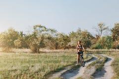 Starken Blondine in einer bunten Klage sitzen auf einem Fahrrad in einem Wüstengebiet mit Bäumen und grünem Gras und betrachten d Lizenzfreies Stockbild