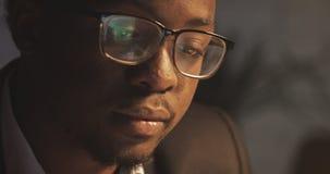 Starker Afroamerikanergesch?ftsmann in den Brillen vor Laptop mit Reflexion der Anzeige in den Brillen stock video
