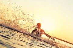 Starker Athlet, der im Wasser bei Sonnenuntergang spritzt Lizenzfreies Stockfoto