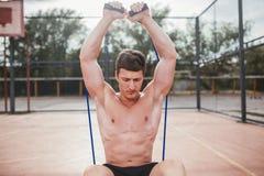 Starker athletischer Kerl trägt Mannausdehnungsexpander zur Schau Stockfoto