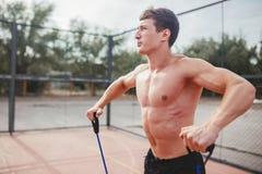 Starker athletischer Kerl trägt Mannausdehnungsexpander zur Schau Lizenzfreie Stockfotografie