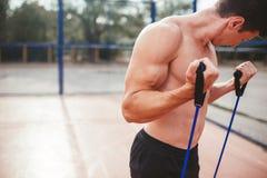 Starker athletischer Kerl trägt Mannausdehnungsexpander zur Schau Lizenzfreies Stockbild
