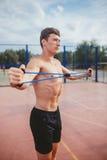 Starker athletischer Kerl trägt Mannausdehnungsexpander zur Schau Stockfotos