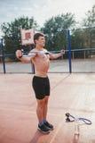 Starker athletischer Kerl trägt Mannausdehnungsexpander zur Schau Stockbild