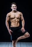 Starker athletischer Mann, der auf dem einem Bein baalncing ist Dunkler Hintergrund Stockfotos