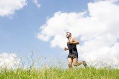 Starker athletischer Mann, der auf dem Feld läuft stockfotos