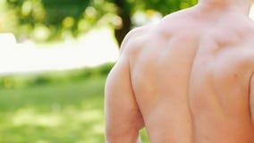 Starker athletischer Mann mit dem muskulösen Torso aufwärmend im Park stock footage