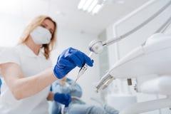 Starker ausgezeichneter Zahnarzt, der das rechte Werkzeug auswählt Stockfoto