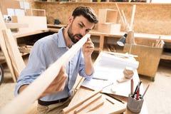 Starker bärtiger jugendlicher Tischler, der bei Tisch herauf Werkstück überprüft Stockbilder