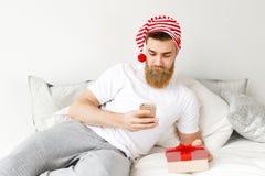 Starker bärtiger junger männlicher Ehemann trägt festlichen Hut, liegt auf Bett, hält Präsentkarton, wie gehend, seins zu beglück Stockfoto