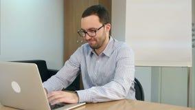 Starker bärtiger junger Mann, der Laptop für das Studieren verwendet stock video