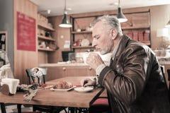 Starker bärtiger Mann, der dem Aroma des Kaffees glaubt stockfotos