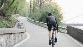 Starker Berufsradfahrer mit den starken Muskeln der d?nnen Beine, die aufw?rts aus dem Sattel heraus reiten Folgen Sie zur?ck Sch stock video