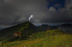 Starker Blitz auf Bergspitze im Wald Stockfoto