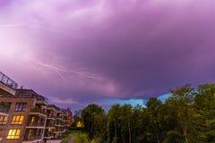 Starker Blitz im purpurroten stürmischen Himmel über modernen Häusern nachts Stockfotografie