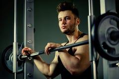 Starker Bodybuilderathlet mit schweren Gewichten in der Turnhalle Stockfotografie