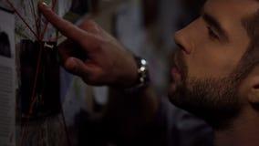 Starker Detektiv, der an Bord kriminelle Ereignisse mit roter Schnur, Links markiert lizenzfreie stockbilder