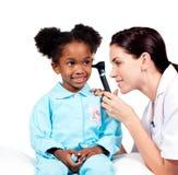 Starker Doktor, der Ohren ihres Patienten überprüft Lizenzfreies Stockbild