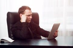 Starker ernster Geschäftsmann, der zu seiner Auflage schaut Lizenzfreie Stockfotos