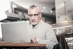 Starker Freiberufler, der gerade seinem Laptop betrachtet lizenzfreie stockbilder