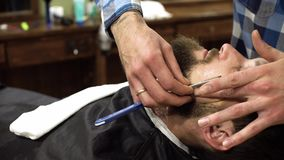 Starker Friseur, der Bart des Kunden mit Friseurrasiermesser rasiert stock video footage