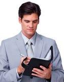 Starker Geschäftsmann, der seine Tagesordnung konsultiert Lizenzfreies Stockbild
