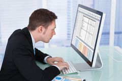 Starker Geschäftsmann, der an Computer im Büro arbeitet Stockbilder