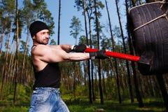 Starker gesunder Erwachsener zerriss Mann mit den großen Muskeln, die Auto tyr schlagen lizenzfreies stockbild