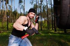 Starker gesunder Erwachsener zerriss Mann mit den großen Muskeln, die Auto tyr schlagen stockfotos