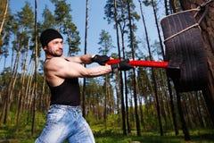 Starker gesunder Erwachsener zerriss Mann mit den großen Muskeln, die Auto tyr schlagen stockbild