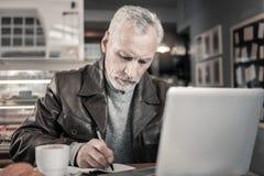 Starker grauhaariger Mann, der Anmerkungen im Schreibheft macht stockbild