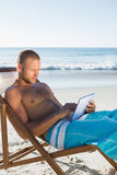 Starker gutaussehender Mann, der seine Tablette beim Ein Sonnenbad nehmen verwendet Lizenzfreie Stockfotografie