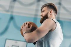 Starker junger Basketball-Spieler, der Ball hält Stockfotografie