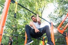 Starker junger Mann, der Einarm ZugUPS beim Hängen an einer Stange im Park tut lizenzfreies stockfoto