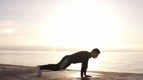 Starker junger Mann, der komplexe Übung tut - Stoß ups und springt oben, in Zeitlupe Mann-Ahlete-Sportler-Trainings-Training stock video