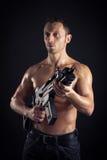 Starker junger Mann mit Gewehr Stockbilder