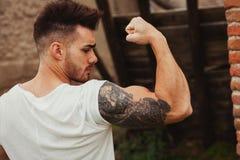 Starker Kerl mit einer Tätowierung auf seinem Arm draußen Lizenzfreies Stockfoto