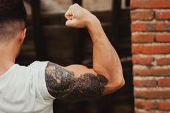 Starker Kerl mit einer Tätowierung auf seinem Arm draußen Stockbild