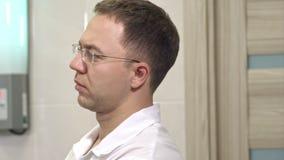 Starker männlicher Chirurg in den Gläsern, die Chirurgie steuern stock footage