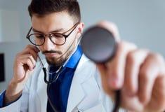 Starker männlicher Doktor, der das Stethoskop mit seinem Patienten verwendet Lizenzfreie Stockbilder