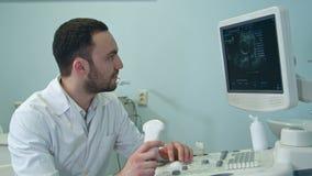 Starker männlicher Doktor, der Ultraschallscan-Ergebnisse betrachtet stock footage