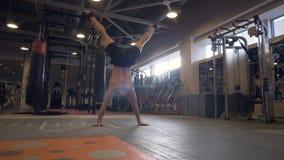 Starker Mann, der auf Händen mit Beine auf Energietrainings-Sportverein oben anheben steht stock footage
