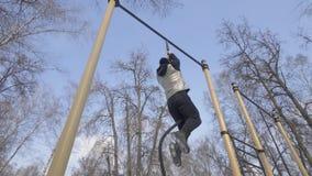 Starker Mann, der auf Seil während Trainings des im Freien auf Sportplatz klettert stockbild