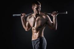 Starker Mann, der Barbell auf seinen Schultern, schauend zur Seite hält Stockfotografie