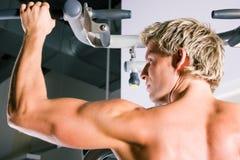 Starker Mann, der in der Gymnastik ausarbeitet Stockbilder