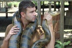 Starker Mann, der gigantische Anakonda hält lizenzfreies stockfoto