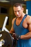 Starker Mann, der seine Trainingsmaschine in der Eignung vorbereitet Stockfoto